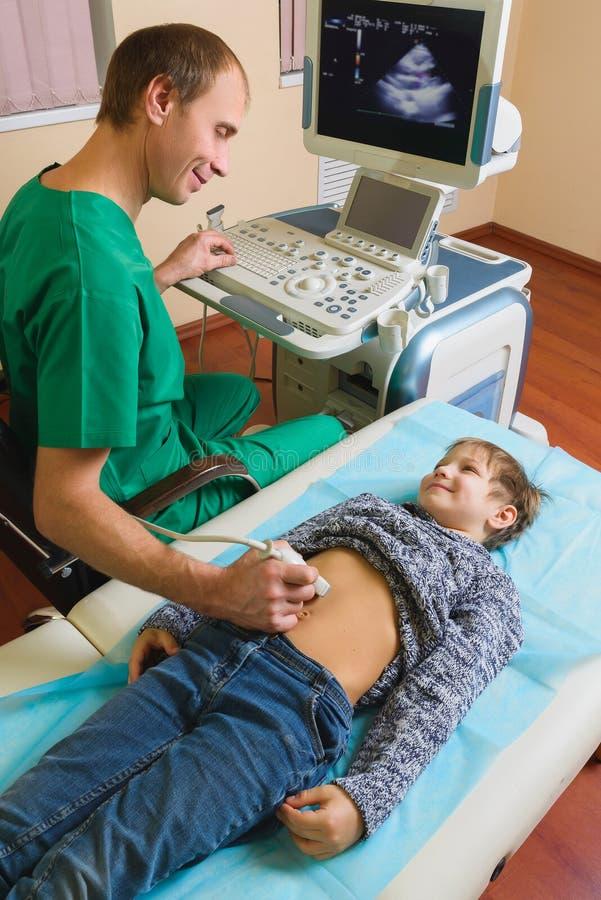 Doktor som analyserar pojkepatienten med magen arkivbilder
