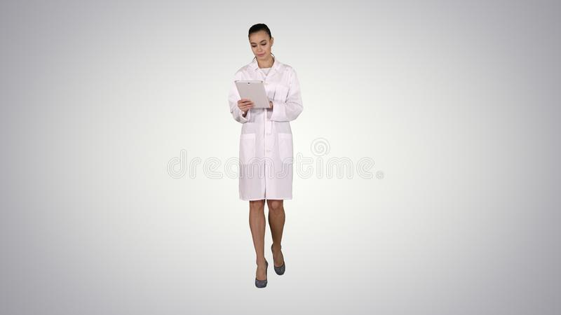 Doktor som använder minnestavlan, medan gå på lutningbakgrund royaltyfri fotografi