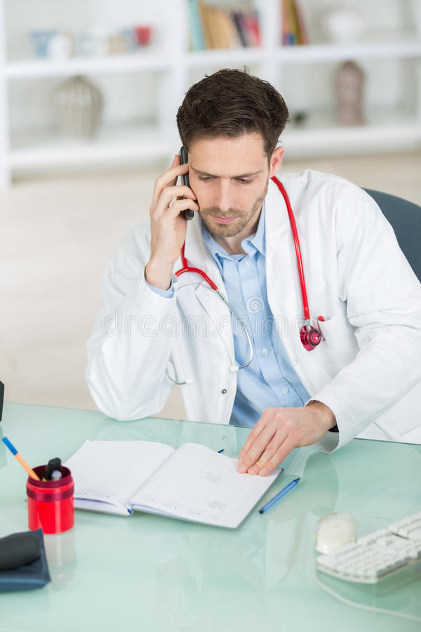Doktor som använder mobiltelefonen för att diskutera labbresultat royaltyfri foto