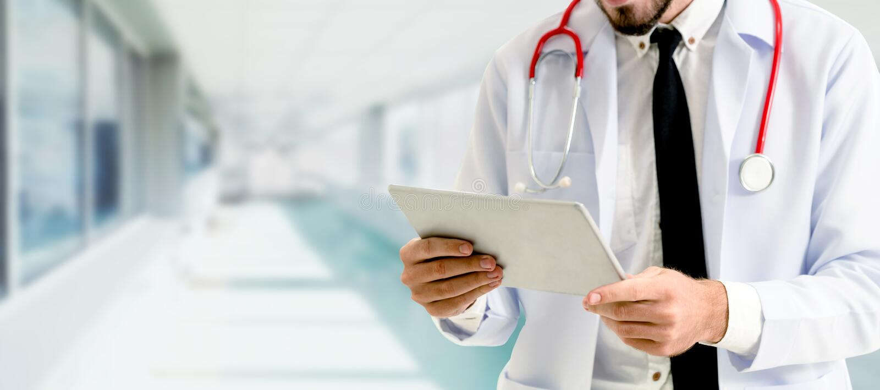 Doktor som anv?nder minnestavladatoren p? sjukhuset royaltyfri bild