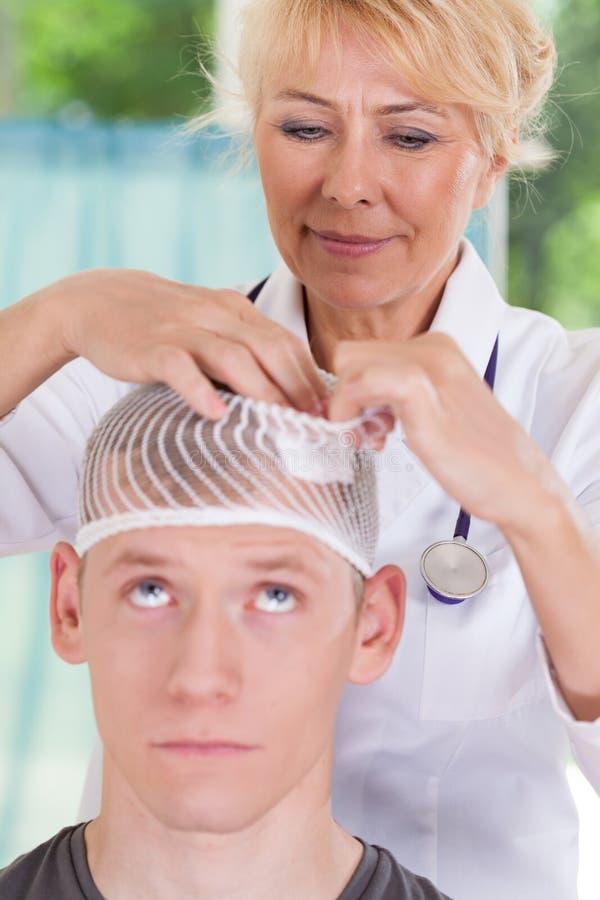 Doktor som applicerar dressingen efter den head skadan arkivfoton