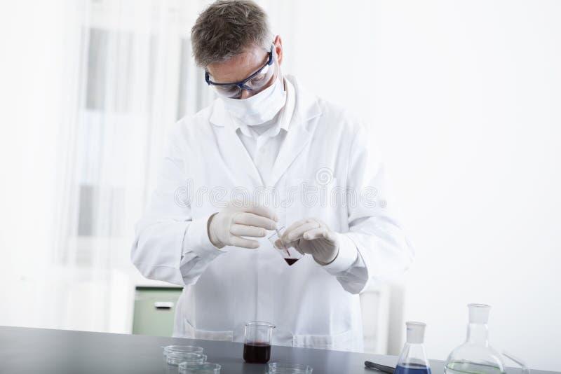 Doktor som arbetar med mikroskopet och blod fotografering för bildbyråer
