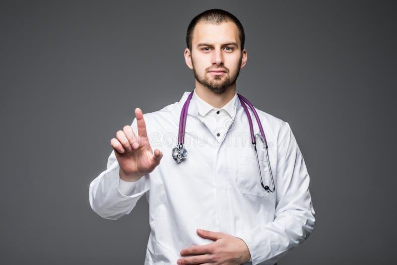 Doktor som arbetar på genomskinligt wipebräde Manipulera det rörande genomskinliga wipebrädet med fingret, medan stå mot grå back royaltyfri bild