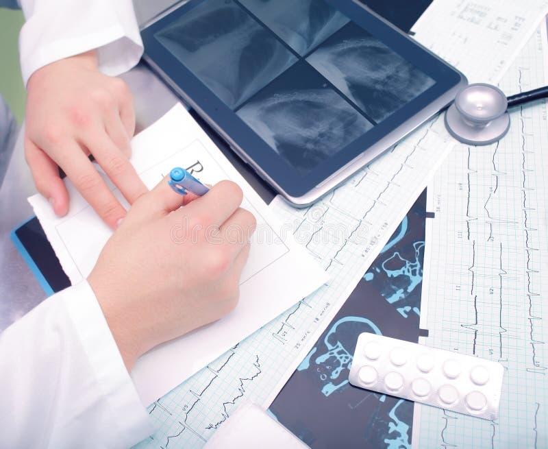 Doktor som arbetar på hans skrivbord arkivfoton