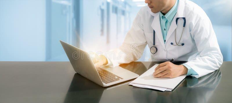 Doktor som arbetar på skrivbordet med bärbara datorn arkivbilder