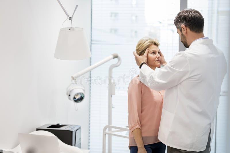 Doktor som behandlar den mogna patienten på sjukhuset royaltyfri foto