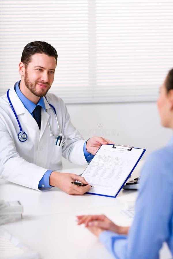 Doktor som ber häftet av en patient royaltyfri foto