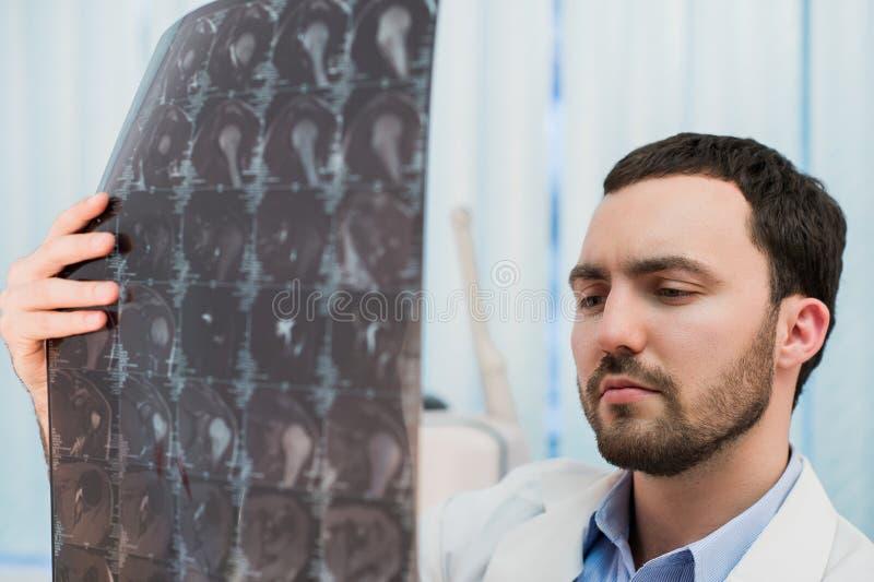 Doktor som beskådar MRI-bildläsningar på hans kontor royaltyfri fotografi