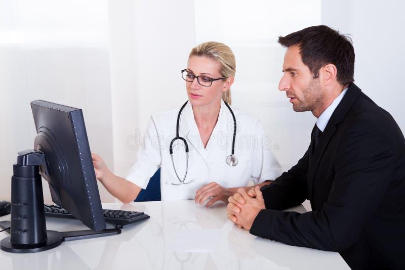 Doktor som förklarar något till en manlig patient royaltyfri foto
