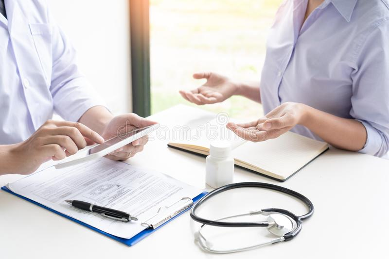 Doktor som förklarar och ger en konsultation till tålmodiga medicinska informationer och diagnos om behandlingen för villkor i H arkivfoto
