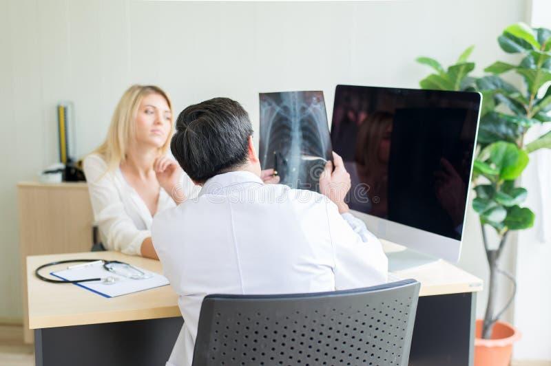 Doktor som förklarar och kontrollerar röntgenstrålefilmen till den kvinnliga patienten i sjukhus, tillbaka sikt och selektiv foku royaltyfria foton