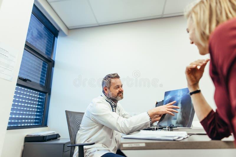 Doktor som förklarar röntgenstrålen till den kvinnliga patienten royaltyfria foton