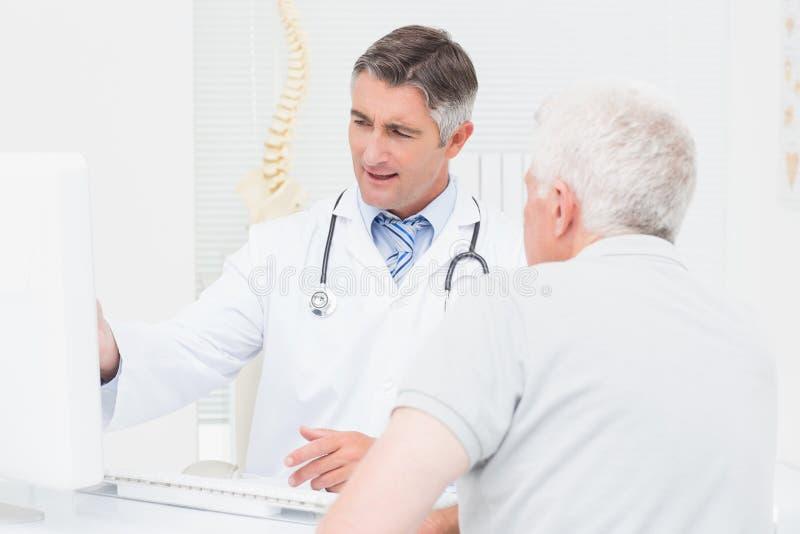 Doktor som förklarar rapporter till den höga patienten på datoren royaltyfri fotografi