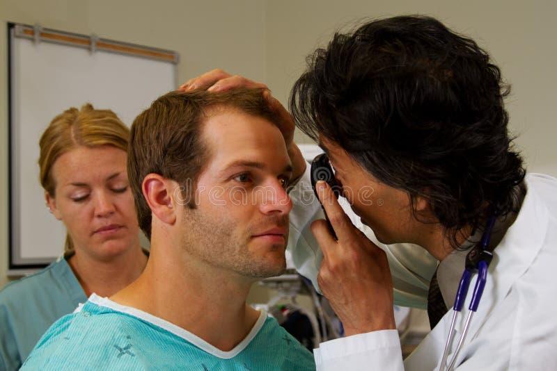 Doktor som gör ögonundersökning royaltyfri bild