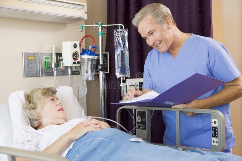 doktor som gör anmärkningar den patient höga kvinnan arkivbild