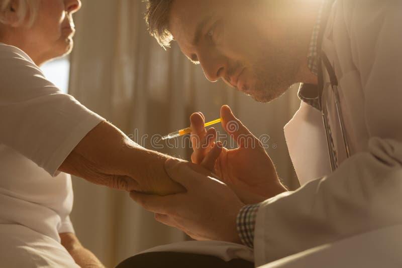 Doktor som gör en injektion royaltyfri fotografi