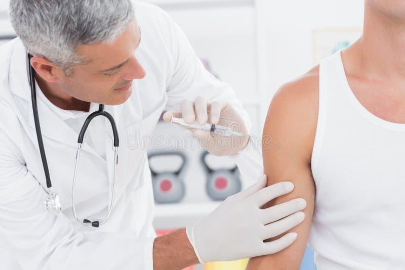 Doktor som gör en injektion till hans patient royaltyfria foton