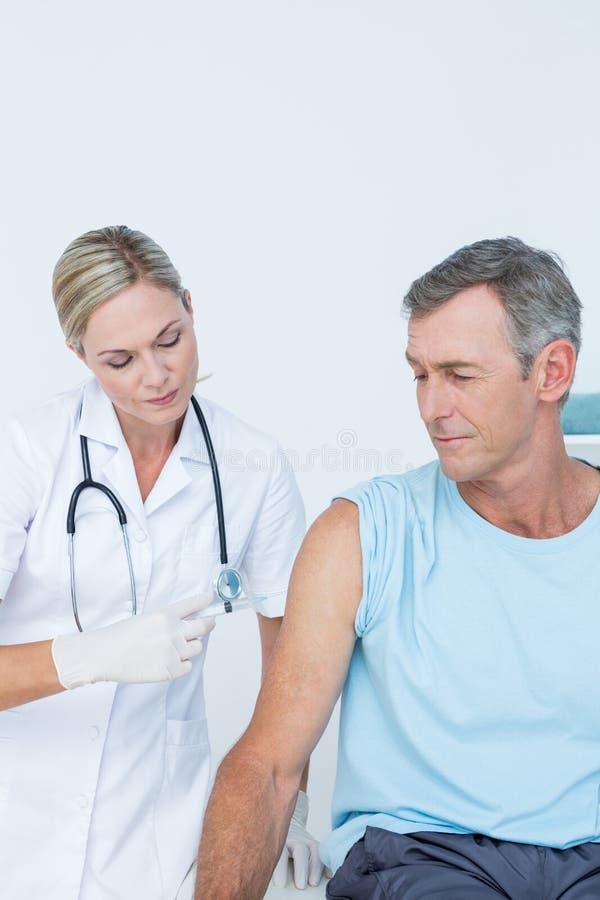 Doktor som gör en injektion till hennes patient royaltyfria foton