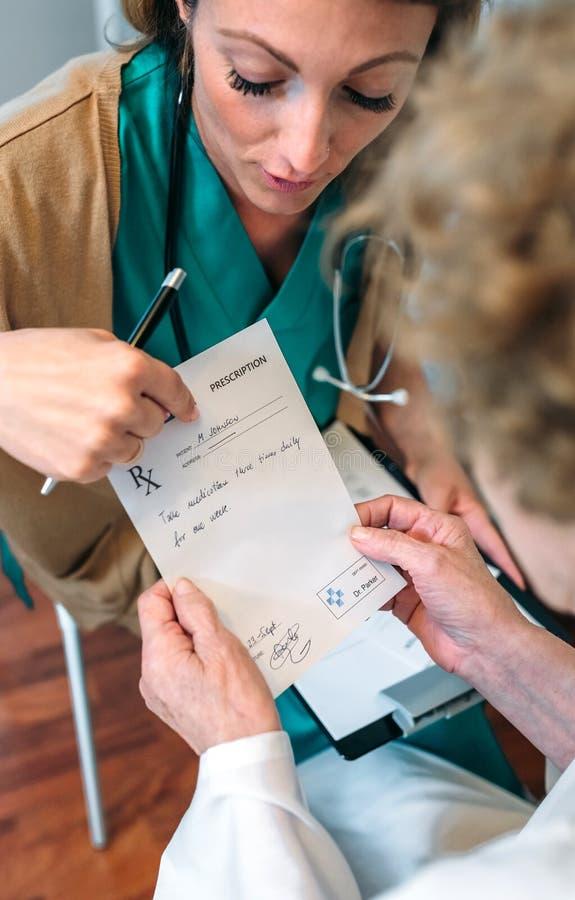 Doktor som ger ett recept till den höga patienten arkivfoton