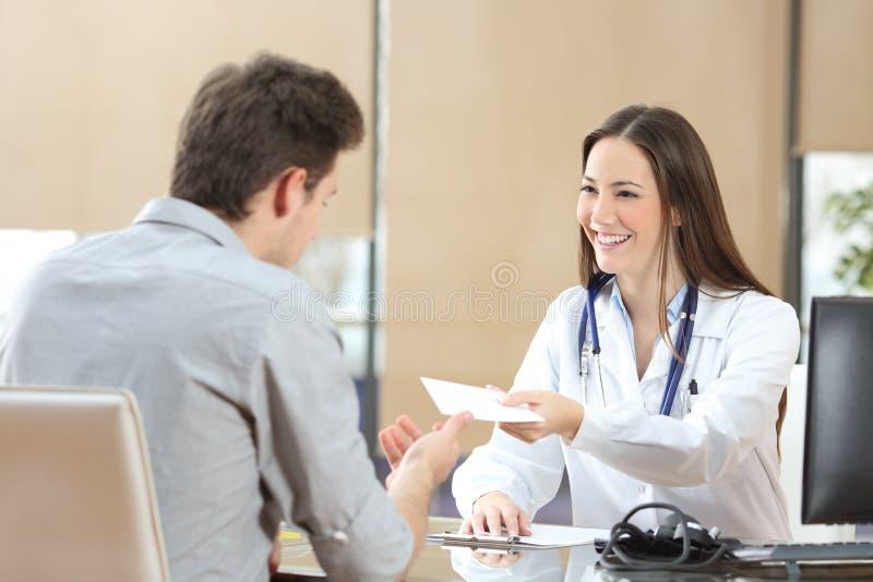 Doktor som ger ett recept till hennes patient arkivbild