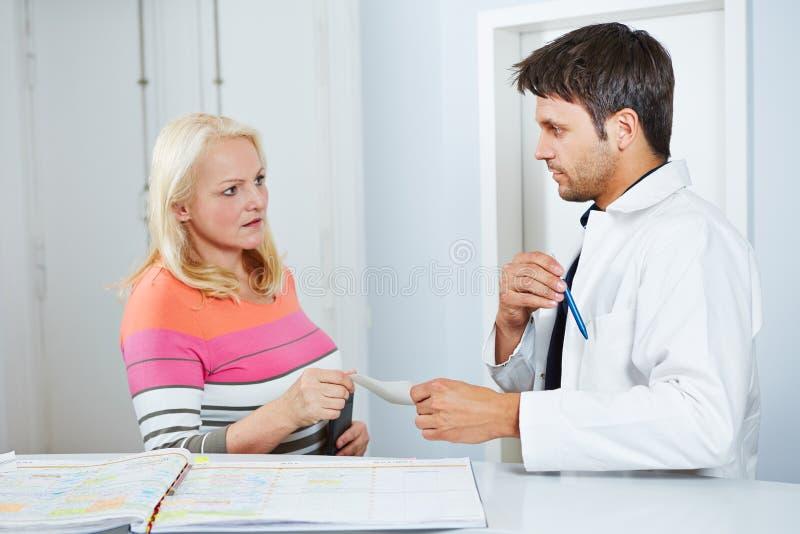 Doktor som ger hög kvinna ett recept arkivbild