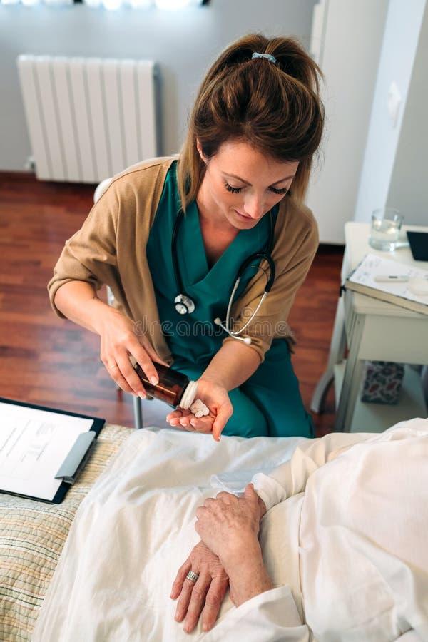 Doktor som ger läkarbehandlingdosen till den äldre patienten arkivbilder