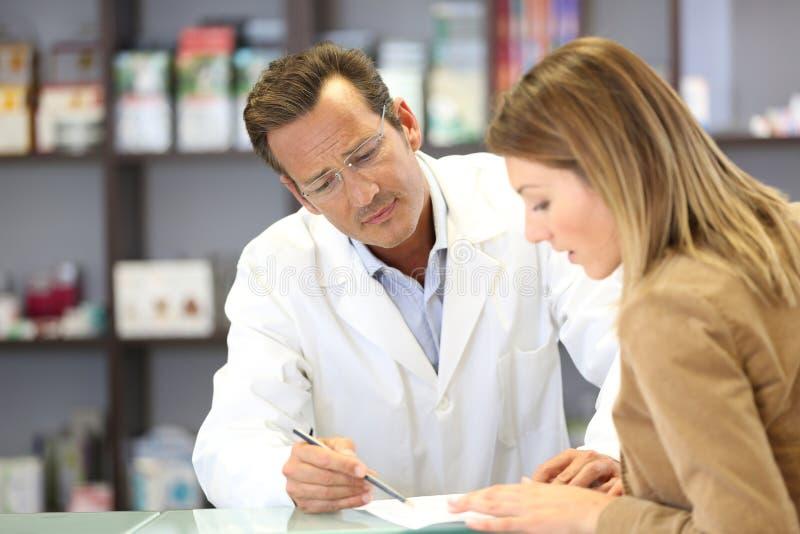 Doktor som ger medicinsk rådgivning till patienten royaltyfria bilder