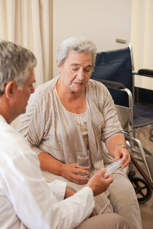 Doktor som ger pills till hans tålmodig arkivfoto