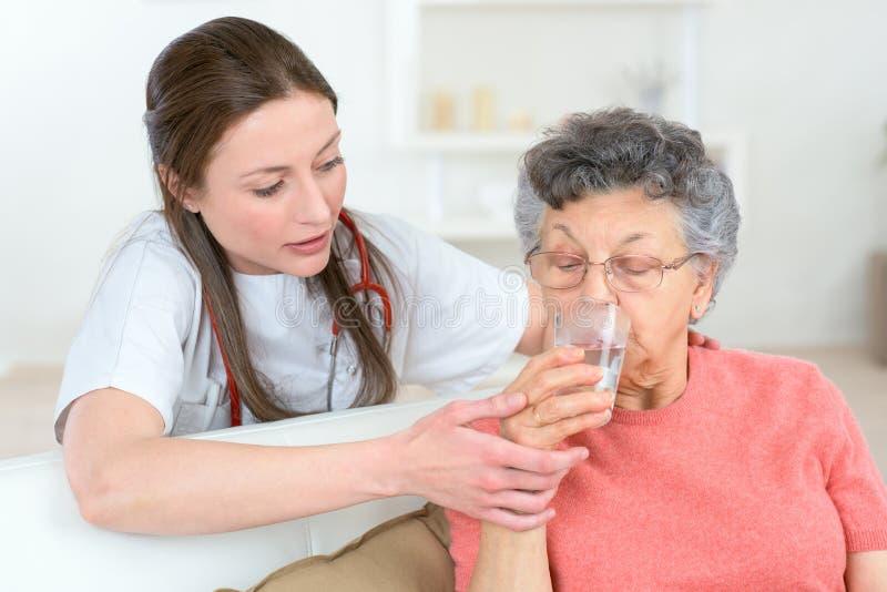 Doktor som ger sjuk hög kvinna glass vatten royaltyfri bild