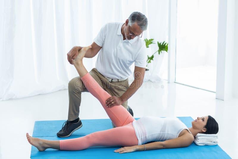 Doktor som ger sjukgymnastik till gravida kvinnan royaltyfria foton