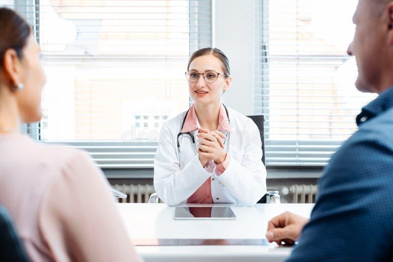 Doktor som har konsultation med två patienter royaltyfri fotografi