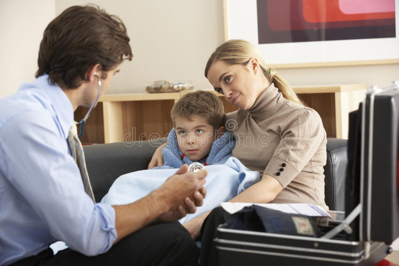 Doktor som hemma besöker det sjuka barnet och modern arkivbild