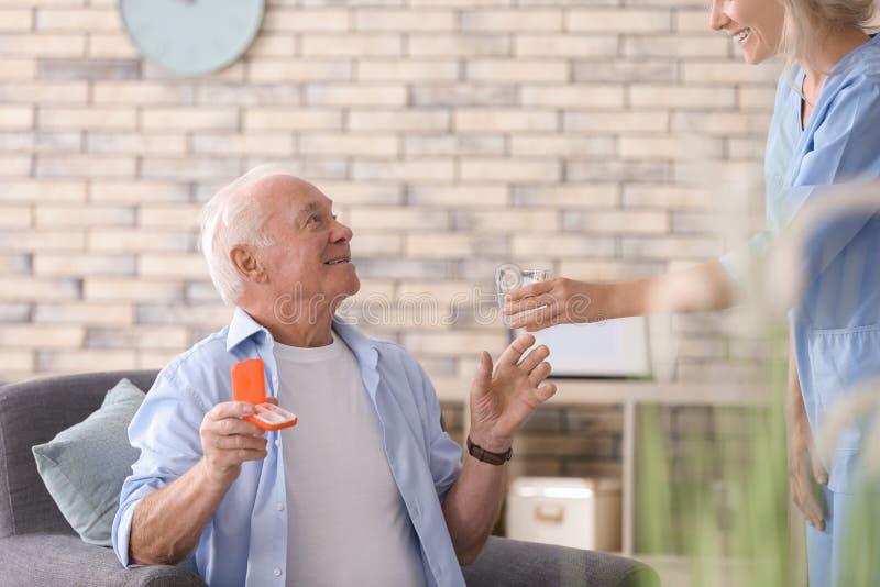 Doktor som hemma ger medicin till den höga mannen royaltyfria foton