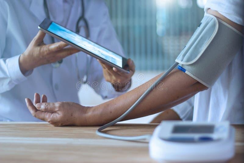 Doktor som kontrollerar blodtryck av äldre patient via minnestavlan på händer i sjukhus royaltyfri foto