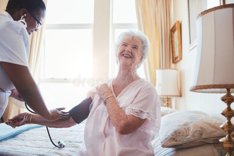 Doktor som kontrollerar blodtryck av en hög kvinna royaltyfria bilder