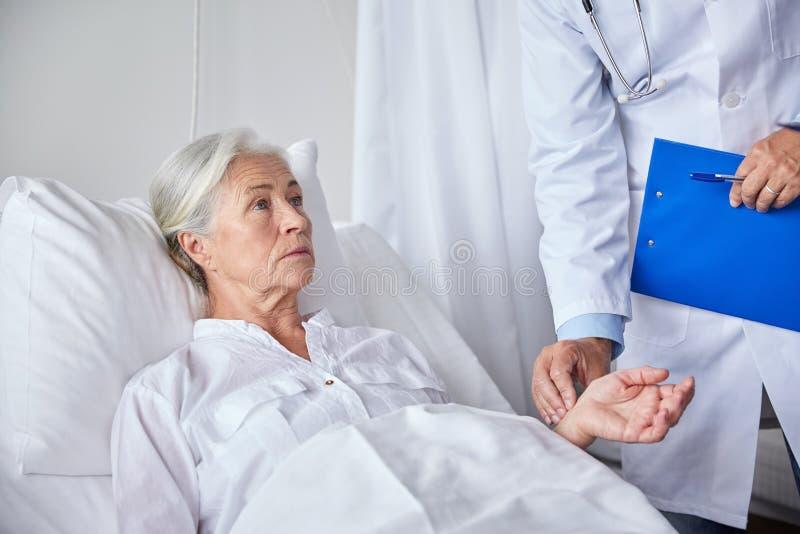 Doktor som kontrollerar hög kvinnapuls på sjukhuset arkivbild
