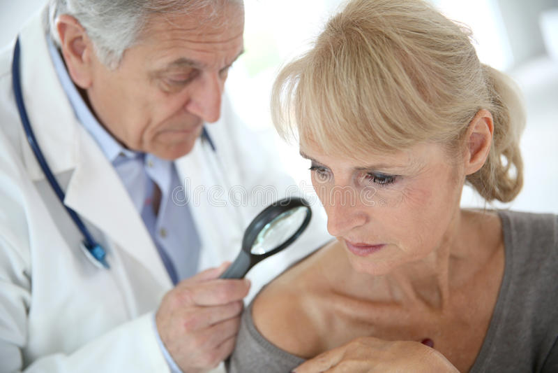Doktor som kontrollerar kvinnas hud arkivbild