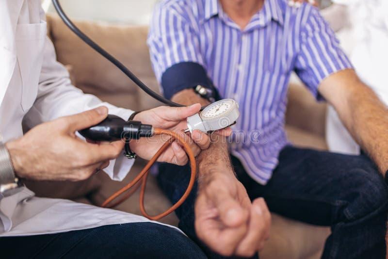 Doktor som kontrollerar tålmodigt arteriellt blodtryck för gamal man royaltyfri foto