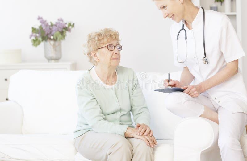 Doktor som ler till den äldre patienten arkivfoton