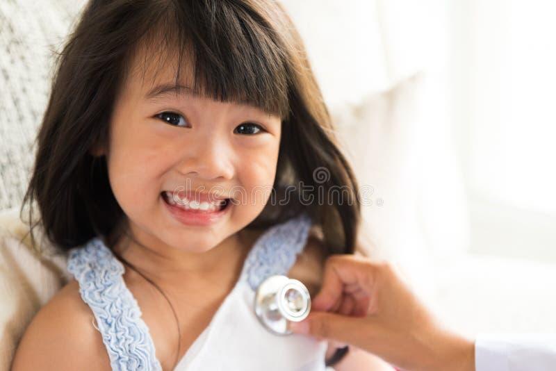 Doktor som lite undersöker flickan, genom att använda stetoskopet arkivbild