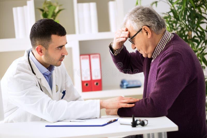 Doktor som lyssnar till patienten som förklarar hans smärtsamt arkivfoton