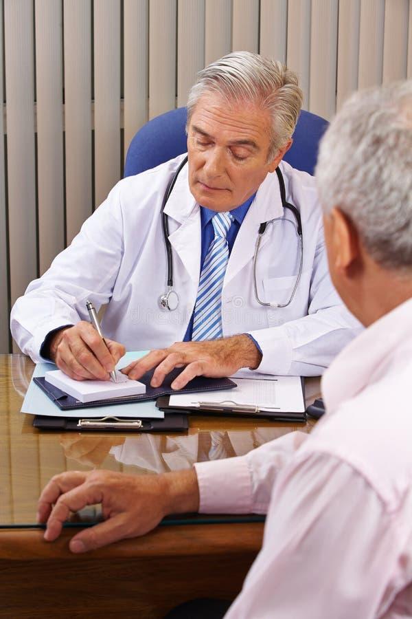 Doktor som lyssnar till tålmodign och tar anmärkningar royaltyfri foto