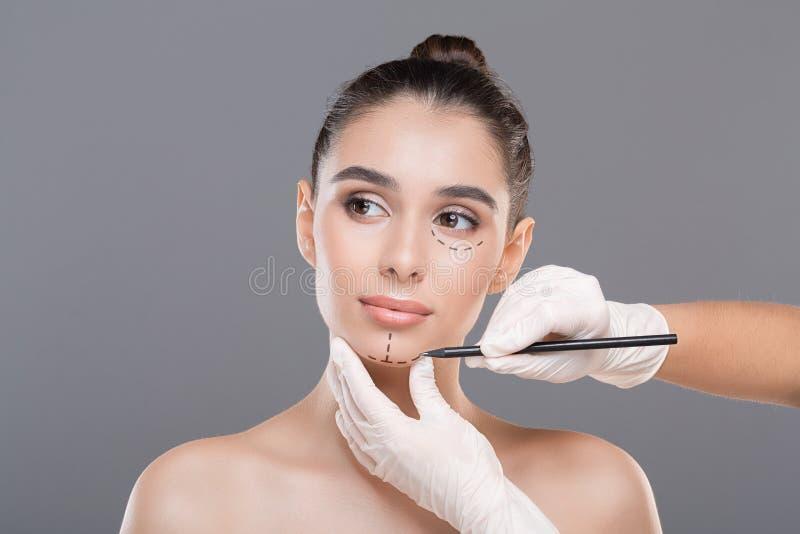 Doktor som markerar framsidan f?r ung kvinna f?r kosmetisk kirurgi arkivfoto