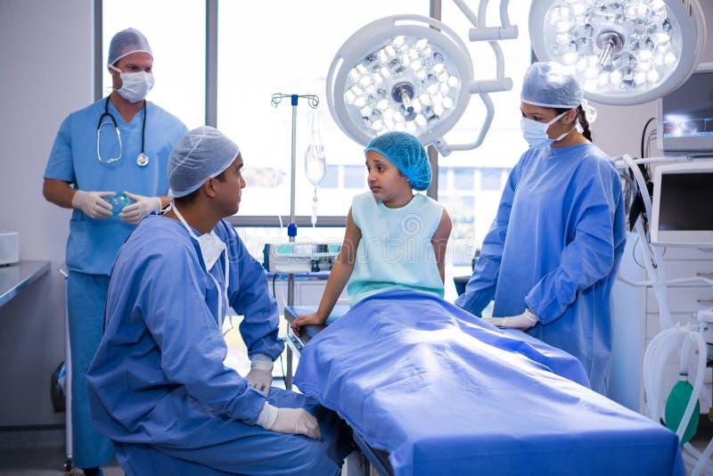 Doktor som påverkar varandra med patienten i operationrum royaltyfri bild