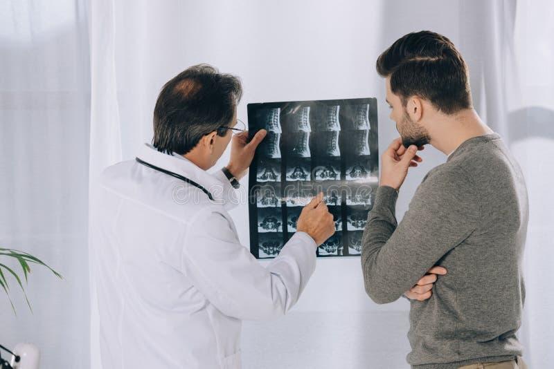 doktor som pekar på den manliga patienten arkivfoton