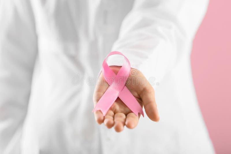 Doktor som rymmer det rosa bandet på färgbakgrund, closeup Rosa band p? corkboard arkivbild