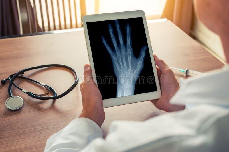 Doktor som rymmer en digital minnestavla med r?ntgenstr?len av en v?nster hand Stetoskop och injektionsspruta p? skrivbordet Oste royaltyfri bild