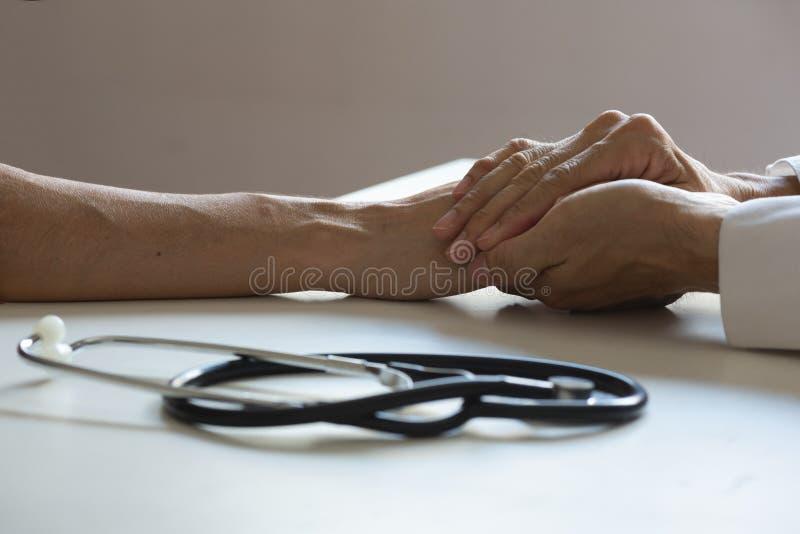 Doktor som rymmer en tålmodig hand i medicinskt kontor arkivfoton