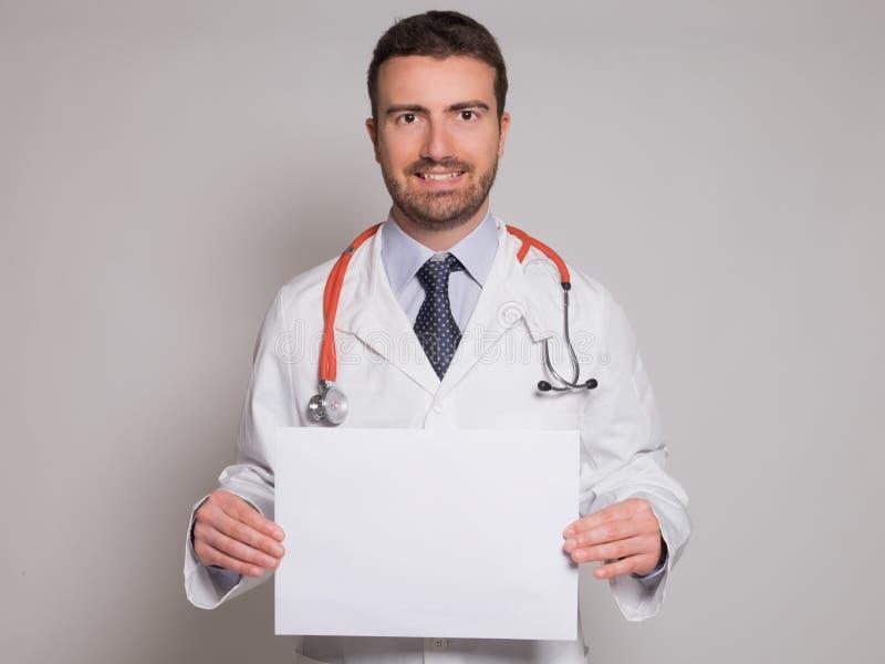 Doktor som rymmer ett vitt pappbaner royaltyfria bilder