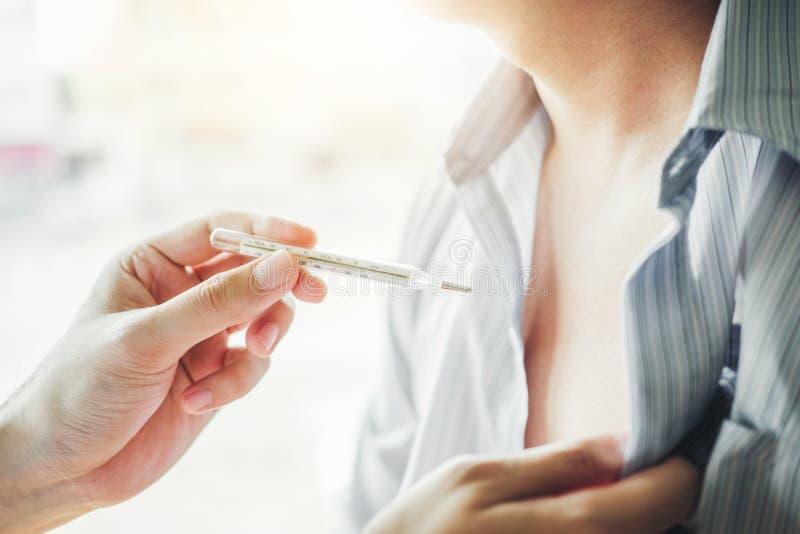 Doktor som rymmer på termometern för att kontrollera sjuk tålmodig hälsovård i sjukhus fotografering för bildbyråer